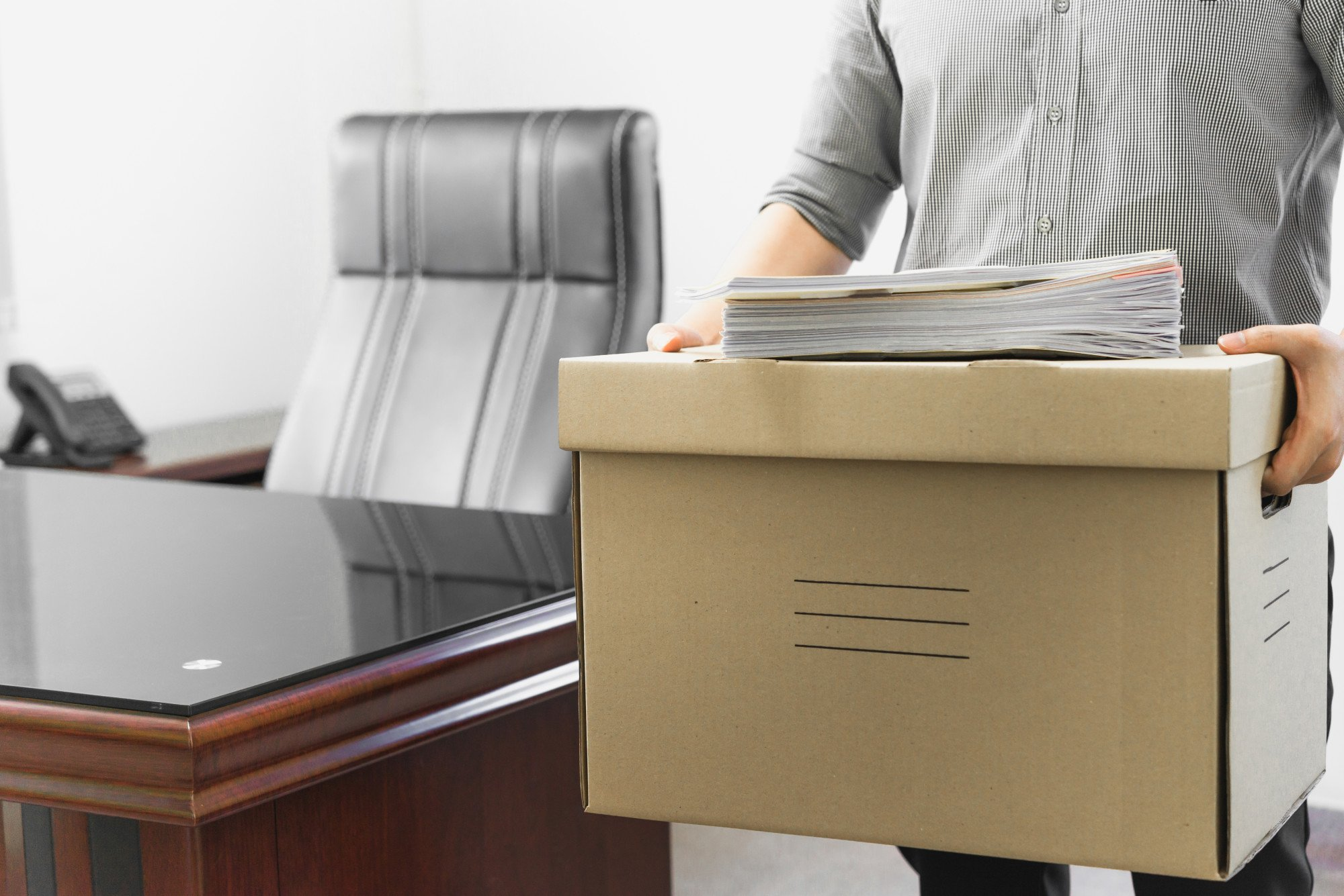 Upset employee packing belongings in box, frustrated stressed man getting fired from job ready to leave on last day at work, sad office worker